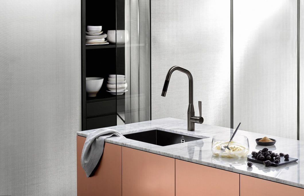 Während Spüle und Kochfeld längst flächenbündig in der Arbeitsplatte verborgen werden, ragt die Küchenarmatur oft aus dem Gesamtbild heraus. Umso besser, wenn sie dann als ästhetisches Designobjekt fungiert - wie hier die Dornbracht Dark Platinum matt, zusammen mit dem neuen glasierten Stahlbecken. (Foto: Dornbracht)