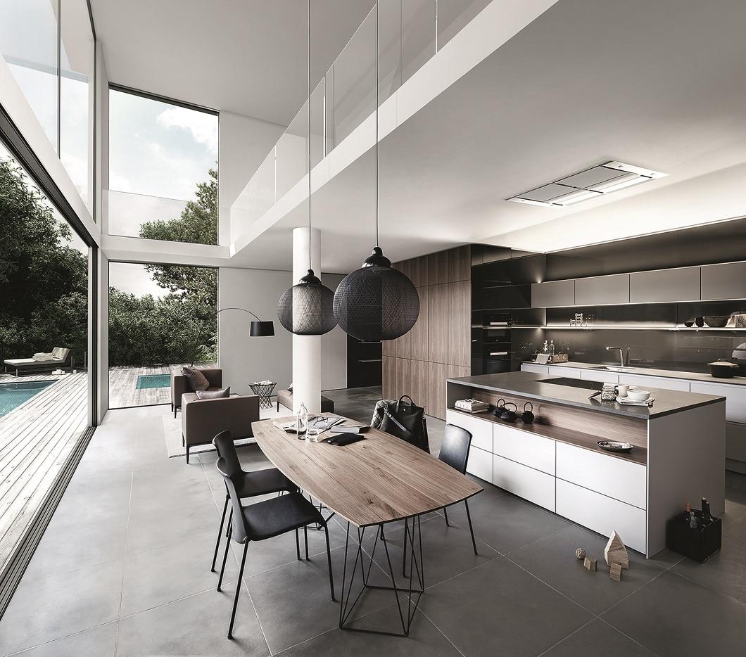 Ein robuster Küchenblock, ein umso zarterer Küchentisch: Die Farbe des Holzes spiegelt sich wieder, die feine Struktur des Tischs gleicht den Küchenraum aus. (Foto: SieMatic)