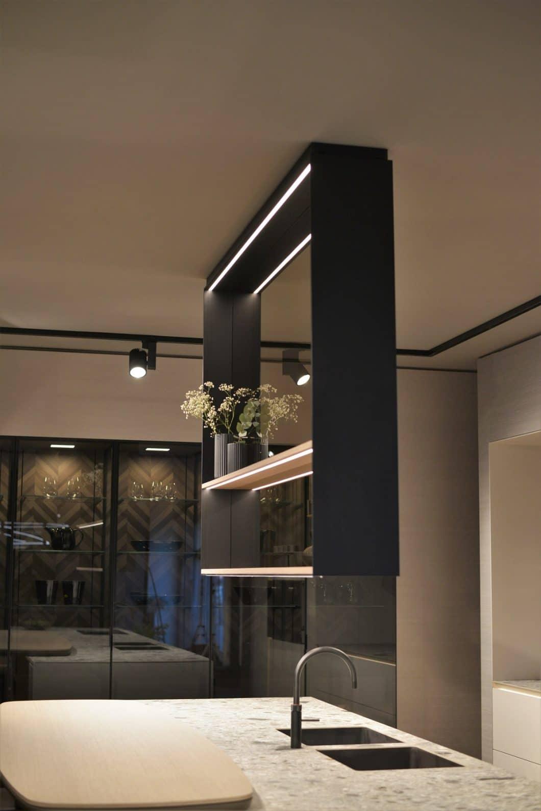Als Raumtrenner fungiert dieses zarte Aluminium-Glas-Gestell, das zwischen Koch- und Essbereich bzw. Bartheke von der Decke hängt und zeitgleich als offenes, modernes Regal fungiert. (Foto: Sophie Engelhard)