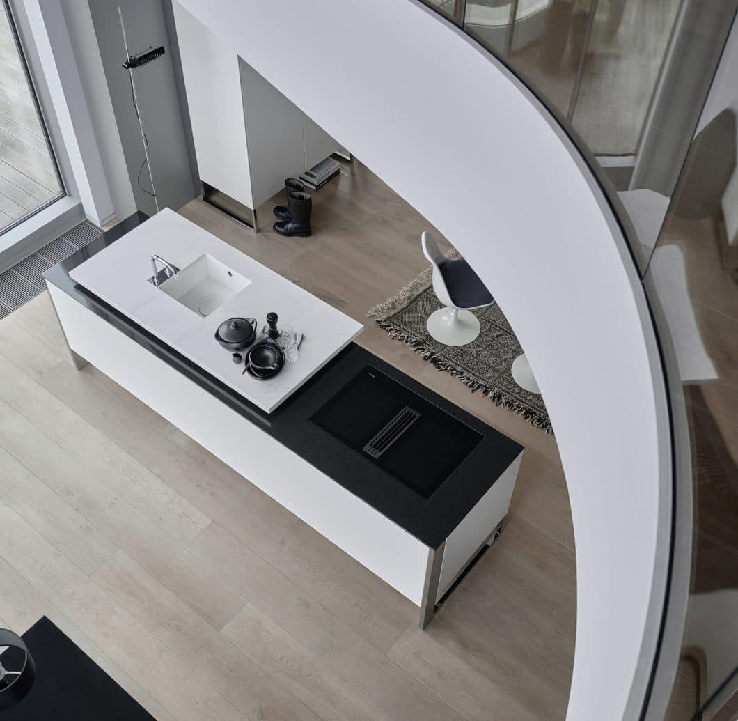 Poggenpohl verleiht der Arbeitsplatte mit seinem neuen Programm +VENOVO 2018 besondere Bedeutung: Die Fläche wird unterteilt in eine herausgehobene Spülfläche und eine Fläche zum Kochen und Arbeiten. (Foto: Poggenpohl)