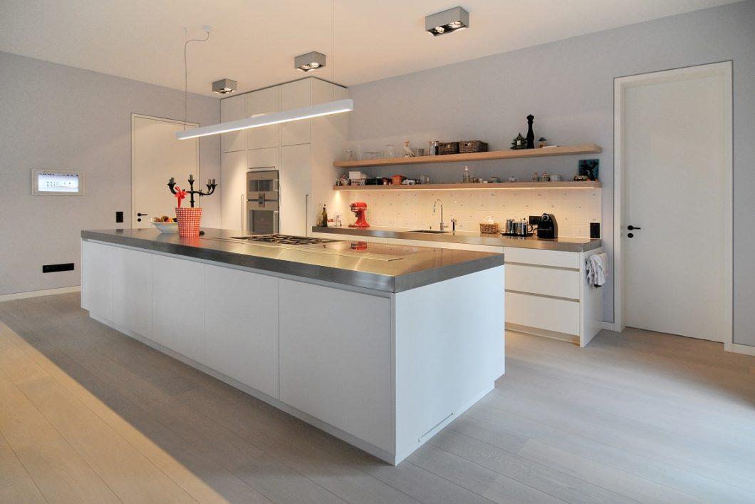 """Dieses Beispiel beweist eindrucksvoll, dass Schreinerküchen nach außen hin mit ganz unterschiedlichen Materialien verkleidet werden können, beispielsweise Mattlack oder Edelstahl. Das hochwertige """"Gerüst"""" aus Holz bleibt verborgen. (Foto: Adam Innenausbau)"""
