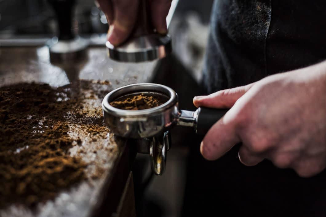 """Beim """"Tampern"""" schmiegen sich die Kaffeepartikel im Siebträger so eng aneinander, dass das Wasser nicht von alleine durchlaufen kann. (Foto: Adobe Stock / Milos)"""