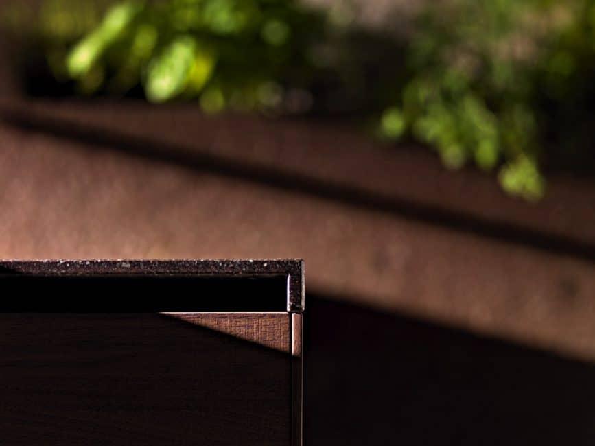 Stark bearbeitete Holzoberflächen mit Struktur und eine Natursteinarbeitsplatte machen dieses Modell der Artematica Noce Tattile aus. Türkanten oder Ecken wurden aus Gründen der Sicherheit und Sauberkeit abgerundet. Küche: Valcucine