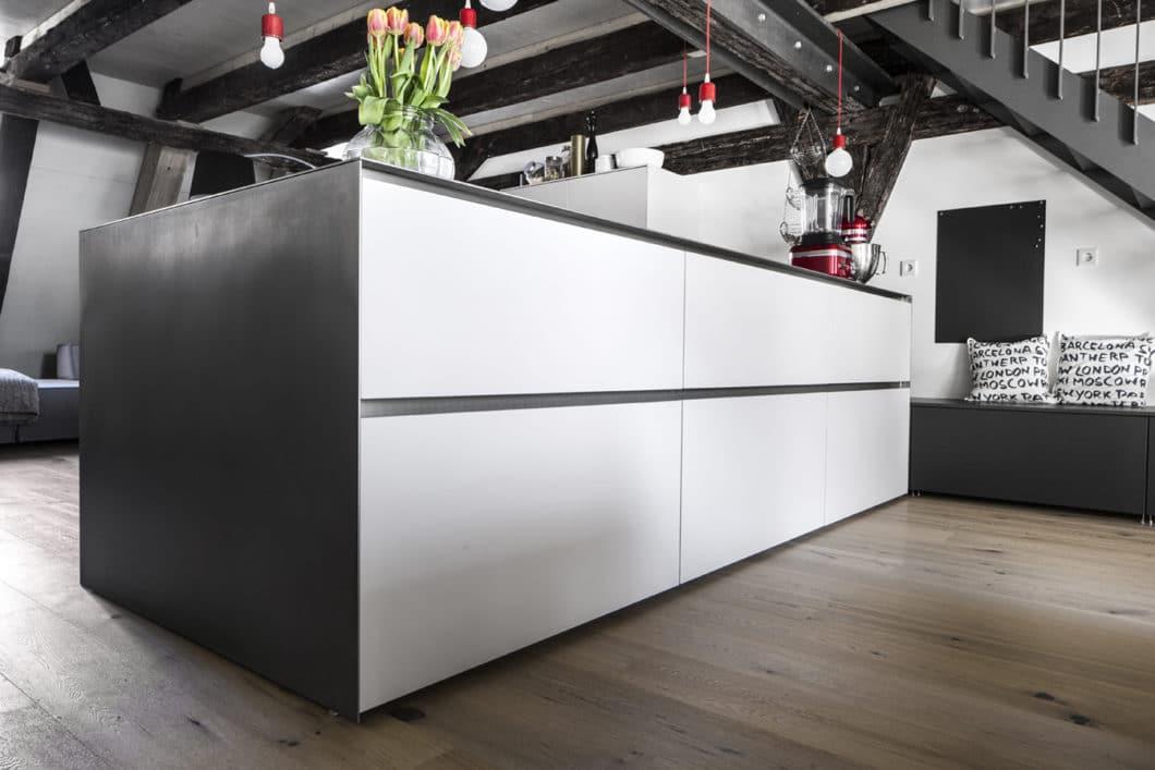 Wohnliche Elemente im puristischen Küchenraum finden sich neben dem hellen Holzparkett in kirschroten Accessoires, wie z.B. die Pendelleuchten und Küchengeräte von KitchenAid. (Foto: Dross Ingolstadt)