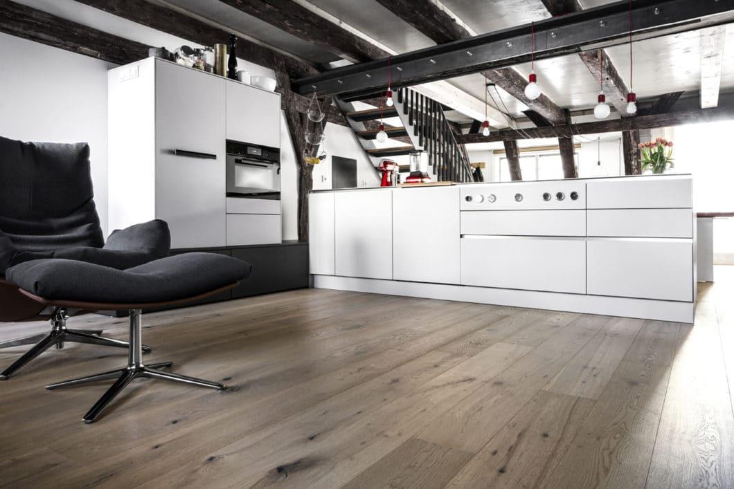 Die Kücheninsel teilt den länglichen Raum genau in zwei Hälften. Vom Kochblock aus blickt man auf den hellen Essbereich, während sich dahinter ein stilvoll eingerichteter Wohnraum anschließt. (Foto: Dross Ingolstadt)