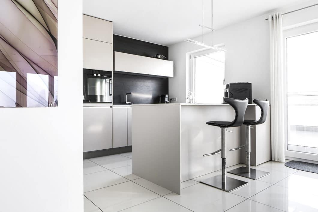Kombinieren Sie Hochschrank und einzelne Oberregale, um eine kleine Küche nicht zu wuchtig wirken zu lassen. Der zusätzliche Beinausschnitt an der Küchenbar verleiht diesem Modell Leichtigkeit. (Foto: Dross Ingolstadt)