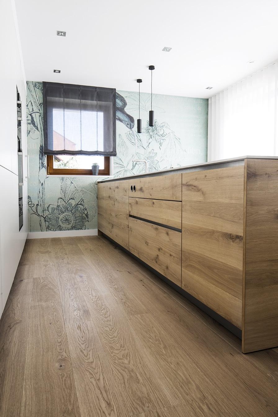 Auf großzügigen 3,60 Meter Länge darf auf dieser Kücheninsel aus Holz gearbeitet werden. Um ein durchgängiges Furnierbild zu erzeugen, wurden die Fronten aus Echtholz handfurniert. (Foto: Dross&Schaffer Ingolstadt)