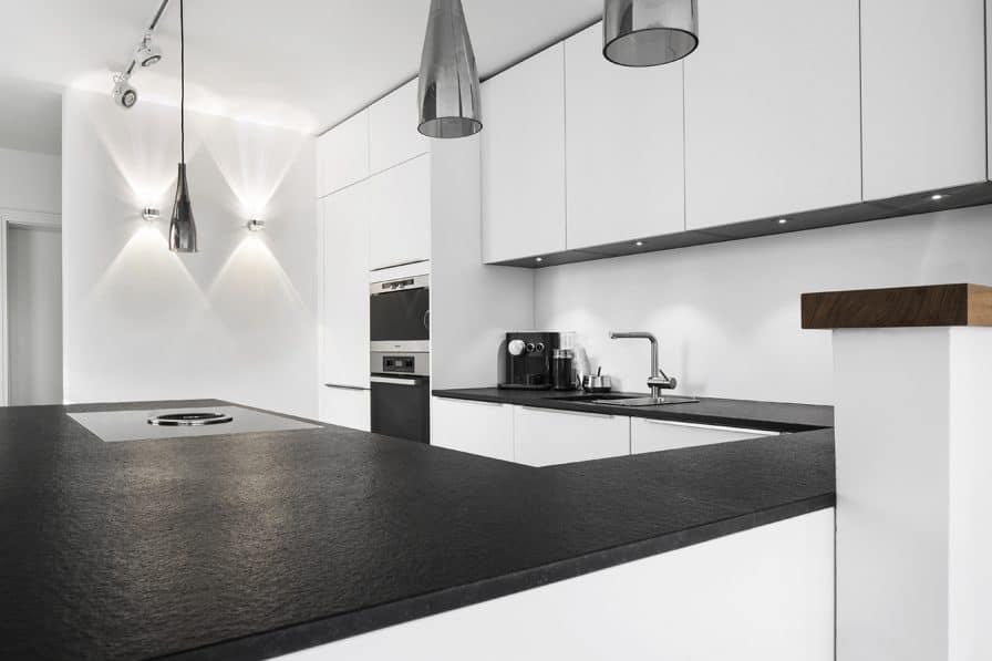 Bei der Planung der modernen Küche legte Marcel Hufnagl von Dross Ingolstadt Wert auf filigrane Details: so findet sich der Edelstahl der Leuchtenkörper in den kaum wahrnehmbaren Griffleisten wieder. Auch das Schwarz des Granits wird erneut aufgegriffen. (Foto: Dross Ingolstadt)