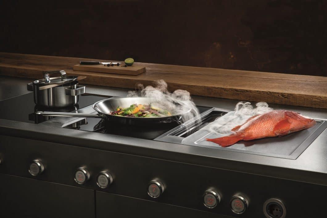 Die erste Schublade dient in der Regel als Blende und kann durch die Technik des Kochfeldabzugs nicht genutzt werden. Im Falle des BORA Professional-Abzugssystems ist sie mit handlichen Drehknebeln versehen, die die Technik griffig steuern. (Foto: BORA)