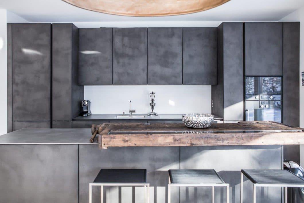 """selektionD-Küchen bieten immer ein bisschen mehr: Innovation, Design und kreative Ideen. (Modell: """"Elegante Coolness"""", betongespachtelte Fronten, Arbeitsplatte aus warm gewalztem Edelstahl, alte Hobelbank als Theke. Foto: selektionD)"""