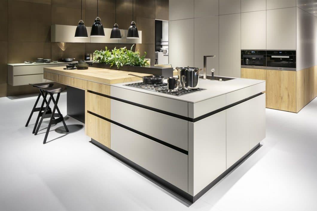 """Beim Modell """"Family"""" von LEICHT übernimmt der Holzeinsatz den """"wohnlichen"""" Teil der Kücheninsel, während die hochwertige Keramikfront- und Arbeitsplatte den """"funktionalen"""" Teil unterstreicht. (Foto: LEICHT Küchen)"""