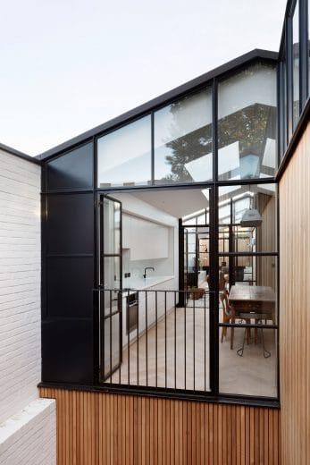 Große Ateliersfenster lassen Licht und Natur herein. Dieser Blick verdeutlicht, wie schmal der Küchenraum eigentlich ist - doch dank der weißen Einbauküche wirkt er aufgeräumt und groß. (Foto: Alex James für De Rosee Sa)