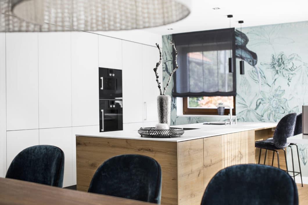 Die moderne Wohnküche arbeitet mit ruhigem Dreiklang aus Holz, Weiß und Schwarz - und setzt mit der floralen Mustertapete in Minzgrün ein unverwechselbares Highlight im Küchenraum. (Foto: Dross&Schaffer Ingolstadt)