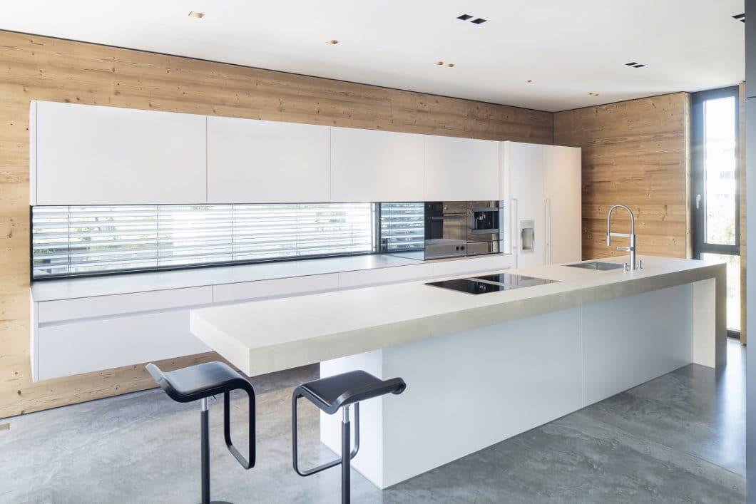 Helle Weißtöne in softem Mattlack, Beigetöne in kräftigem Beton und rustikales Massivholz aus Südtirol harmonieren puristisch und wohnlich zugleich. (Foto: Küchenkunst Einbaukunst)