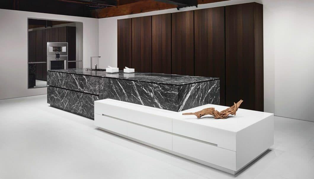 Die Küchen der Manufaktur eggersmann zeichnen sich durch außergewöhnliche Hölzer und Natursteine sowie profilierte Verarbeitung aus. (Foto: eggersmann; Stein: Grigio Carnico)