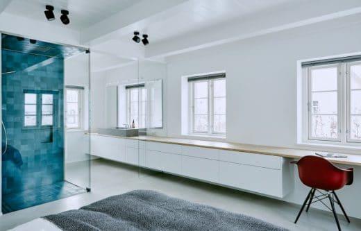 Meerblaue Kacheln im Bad, ein Waschbecken aus feinstem Beton und Badezimmer-Schränke aus rustikaler Eiche: (Auch kalte) Gegensätze ziehen sich an. (Foto: grotheer architektur/ Nina Struve)