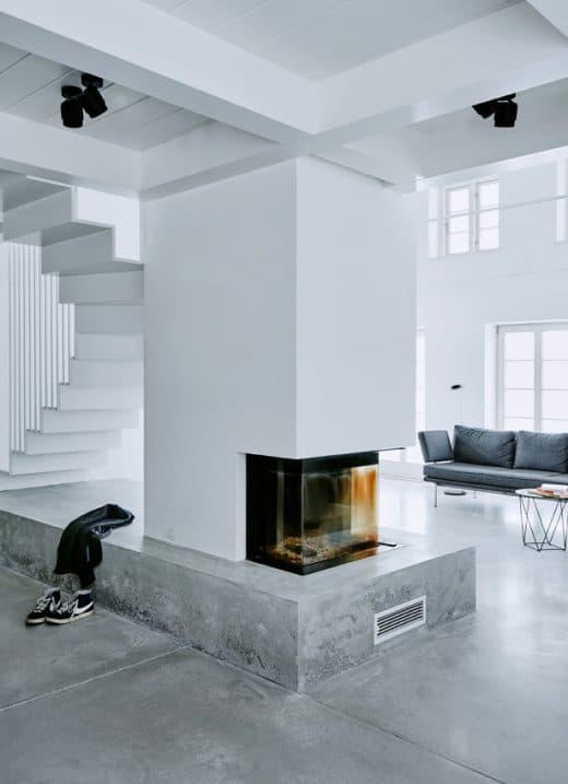 Die Betonplattform um den Kamin herum ist Sockel für die Wendeltreppe und gemütlicher Kaminplatz in einem. (Foto: grotheer architektur/ Nina Struve)