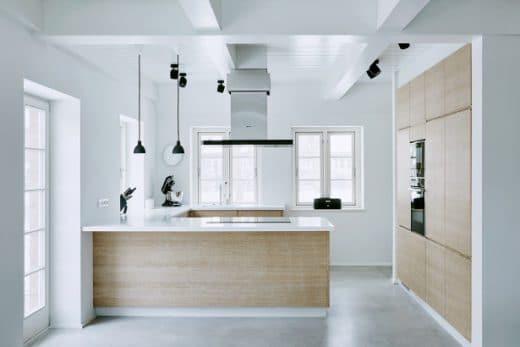 Bildet einen warmen Hingucker in der kühlen Wohnung: Die Küche aus gekalkter Eiche, mit hochwertigen Geräten und weißen feinen Arbeitsplatten. (Foto: grotheer architektur/ Nina Struve)