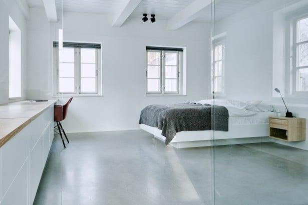 Auch im Schlafzimmer wechseln sich Betonboden und die graublaue Tagesdecke mit warmen Nachttischkommoden ab. (Foto: grotheer architektur/ Nina Struve)