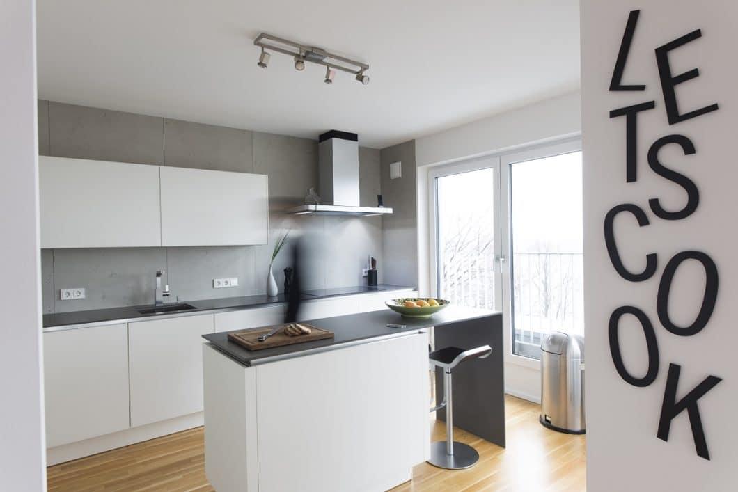 Eine kleine Küche ist mit einer zusätzlichen Kochinsel und Bar-Funktion besser ausgestattet als mit einem raumeinnehmenden Esstisch. (Foto: Jonas küchen kultur köln)