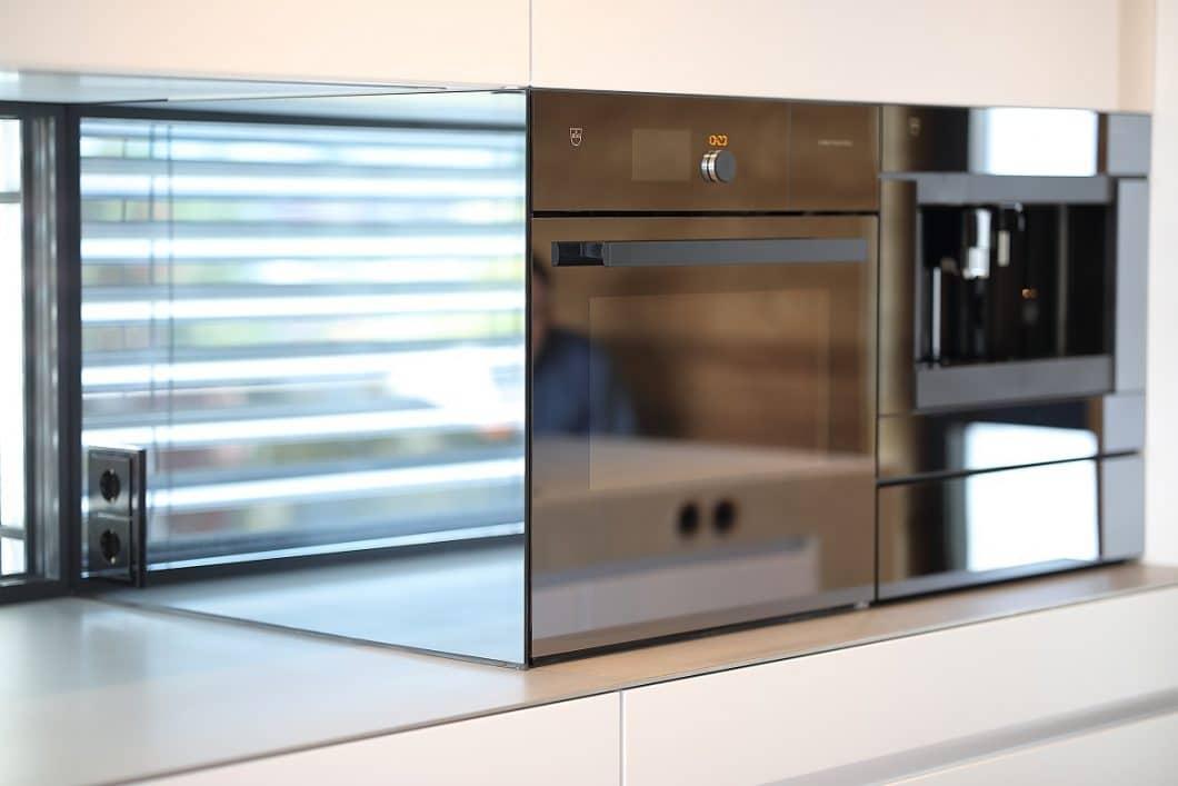 Zu den glatten, ruhigen Mattlackfronten kombiniert das Studio eine 5 mm dünne Edelstahlplatte und einen spiegelnden Geräte-Einschub, der das Panorama von draußen aufgreift. (Foto: Küchenkunst Einbaukunst)