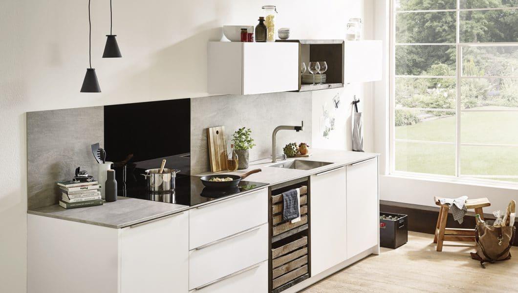 Das Motto Mix & Match steht auch für unterschiedliche Funktionsbereiche (Kochen, Zubereiten etc.), die mit verschiedenartigen Materialien ausgestattet werden. Beispiel: Diese hochwertige Keramik-Arbeitsplatte, die mit einer schwarzen Küchenrückwand aus Glas passend zum Induktionsfeld kombiniert wurde. (Foto: Lechner)