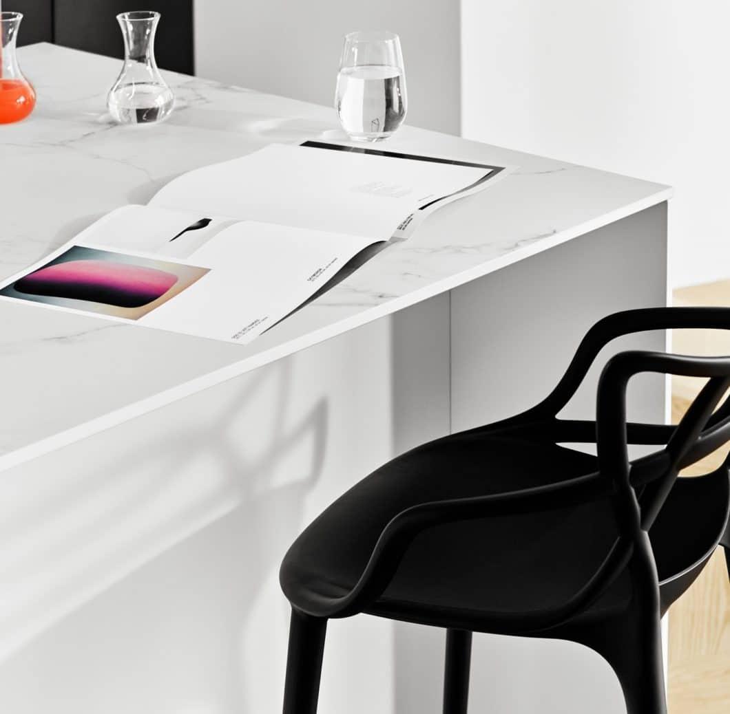 Eine filigrane Keramik-Arbeitsplatte und weißer Mattlack am Inselkorpus gleichen die voluminöse Beton-Wandzeile aus. Ihr Überhang kann als Küchenbar genutzt werden, an der es sich komfortabel auf einem Barhocker sitzen lässt. (Foto: selektionD)