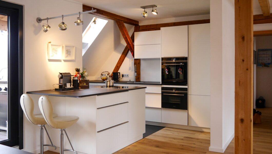 In der Küchenplanung schwingt beim Raumausstattungs-Studio HM Interior auch immer der Blick auf architektonische Einbettung mit. Hier wurde eine hochmoderne Küche sanft in ein historisches Dachgebälk integriert. (Foto: Hammer Margrander)