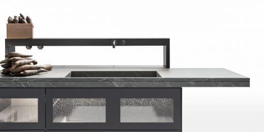 Der hochwertige, schwere Cardoso-Stein als Spüle und feingliedrige Glas bilden einen materiellen Clash und ergänzen sich doch perfekt in Eleganz und Widerstandsfähigkeit. (Foto: Valcucine)