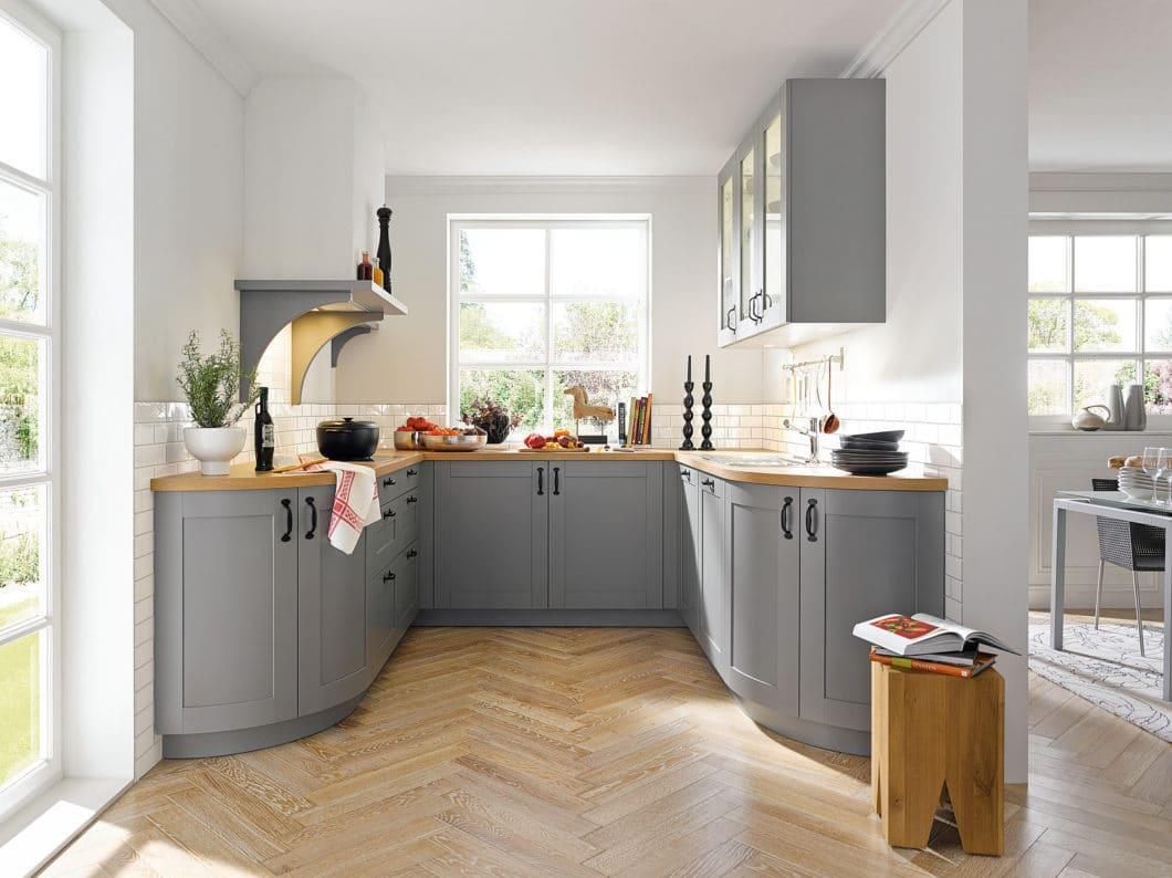 """Elegant gelöst: diese Küche im modernen Landhausstil ist zum Raum hin geöffnet und schließt durch die abgerundeten Eckformen dennoch den """"Bereich Küche"""" ab.. (Foto: Schüller)"""