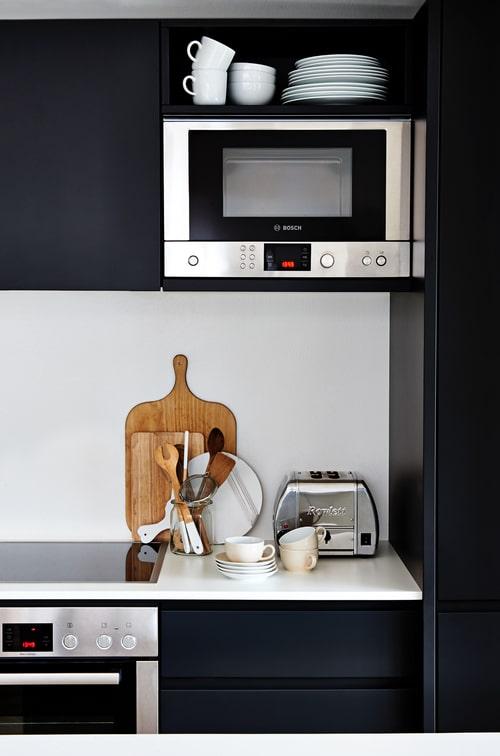 """Schwarz, Metallic und rustikales Holz machen die Küche zu einem seriösen Counterpart, Motto: """"Hart, aber herzlich."""" (Foto: Stefanie Bütow Fotografie)"""