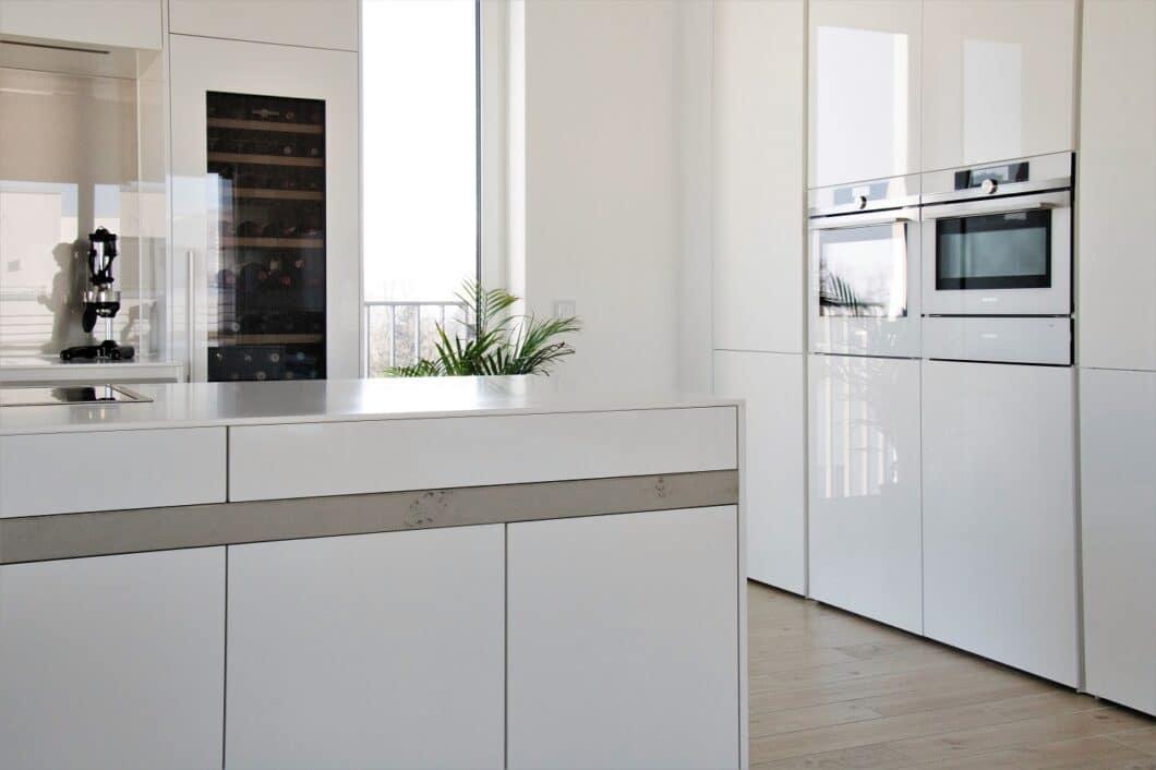 Die flächenbündig integrierten Küchengeräte schmiegen sich perfekt ins ästhetische helle Bild der Küche ein: sowohl Dampfgarer als auch Weinklimaschrank sind in blankem Weiß gehalten. (Foto: Küchenhaus Süd)