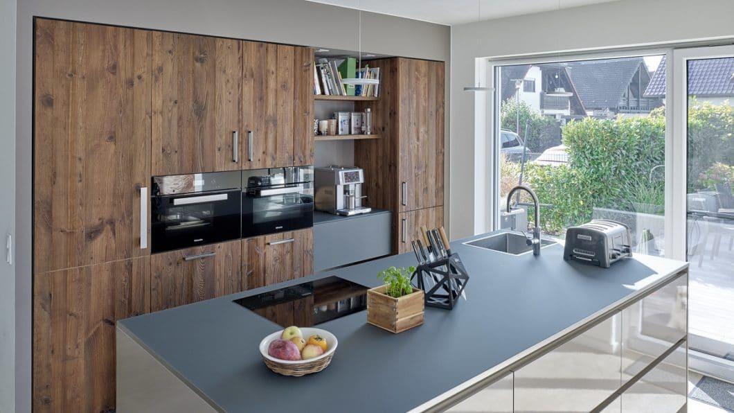 Die Fronten der Kücheninsel wurden beibehalten, aber klar mit einer dunkelgrauen Glasarbeitsplatte in RAL-Farbe abgeschlossen. Diese findet sich in der Zwischennische der Küchenschrankwand wieder. (Foto: KÜCHENPLAN Frankfurt)