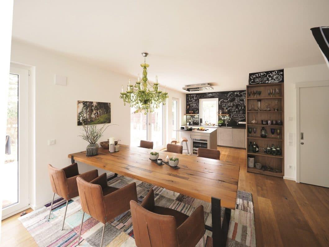Die lichtdurchflutete Küche wird in ihrem Stil im angrenzenden Wohnbereich fortgeführt: der hochwertige Esstisch aus Holz und Stühle mit Stahlgestell verkörpern den Industrie-Stil in ästhetischer Optik. (Foto: küchenART München)