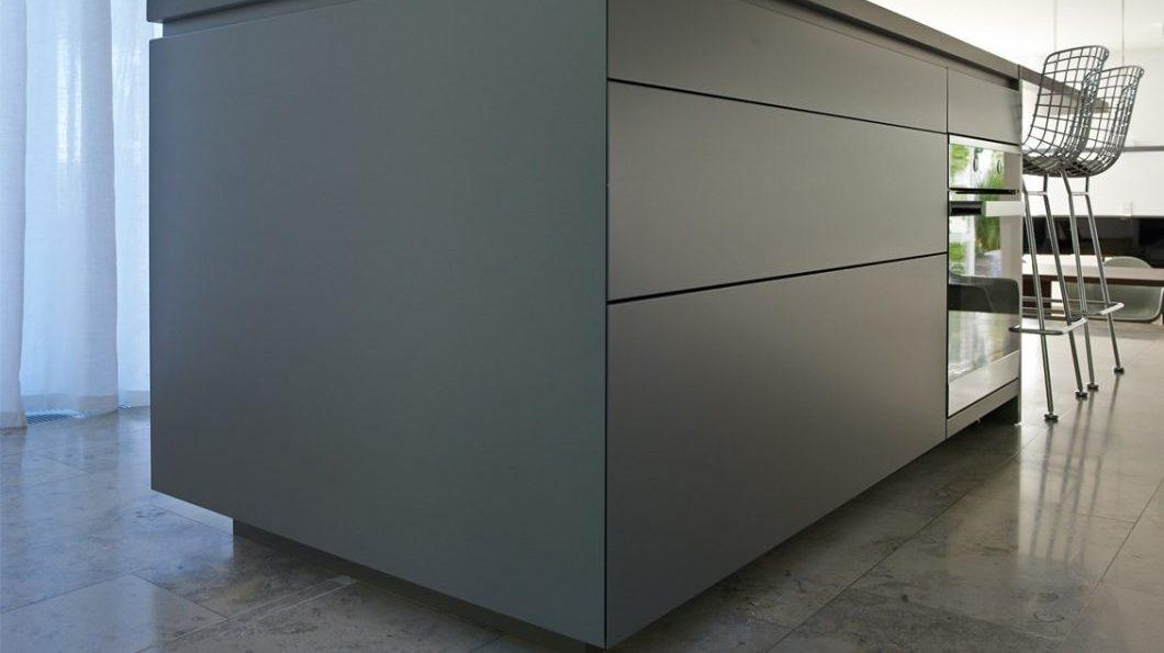 Eine Architekturküche des LAR STUDIO aus Stuttgart. Die graue Küche wurde auf ein Podest im Wohnraum gestellt und somit aus dem Raum hervorgehoben. (Foto: LAR STUDIO)