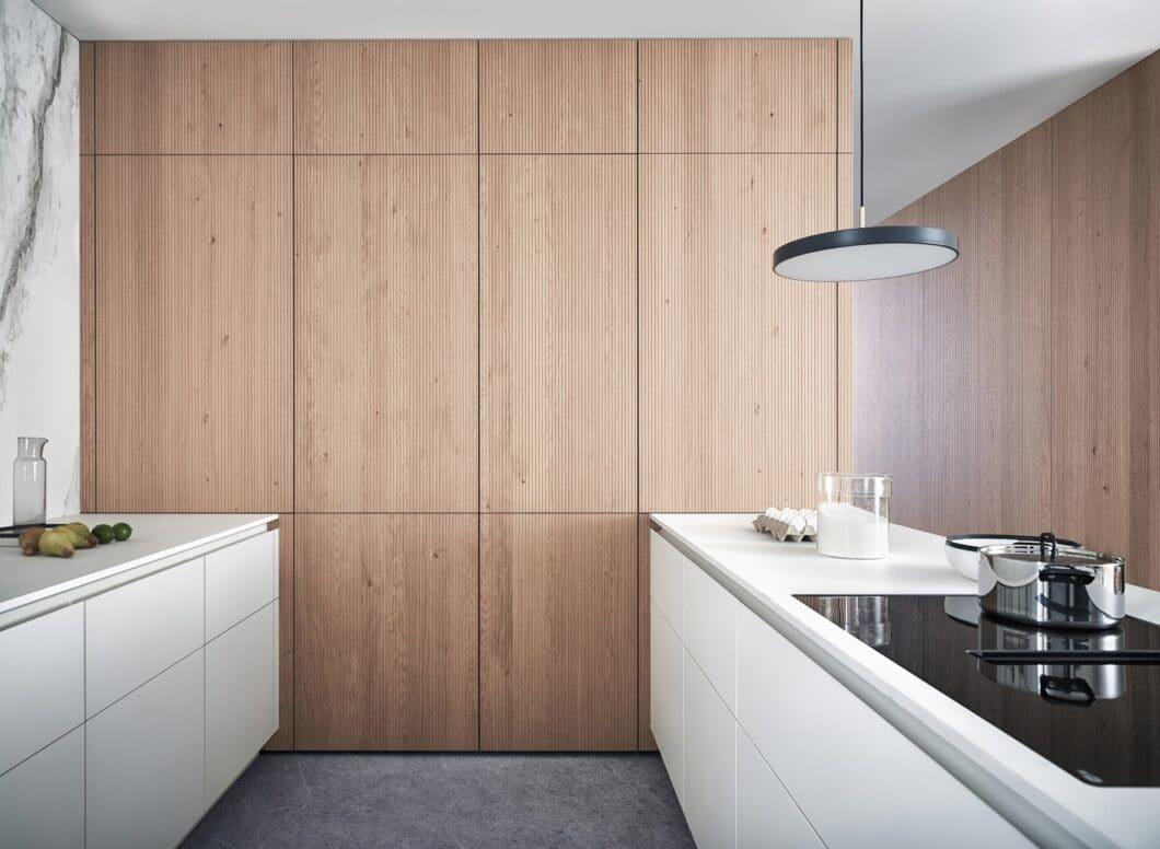 """Die erfrischend natürlichen, hellen Streben von """"Bossa"""" in Eichenoptik werden zu einem lichten Küchenraum mit grifflosen Mattlackfronten aus Fenix kombiniert. (Foto: LEICHT)"""