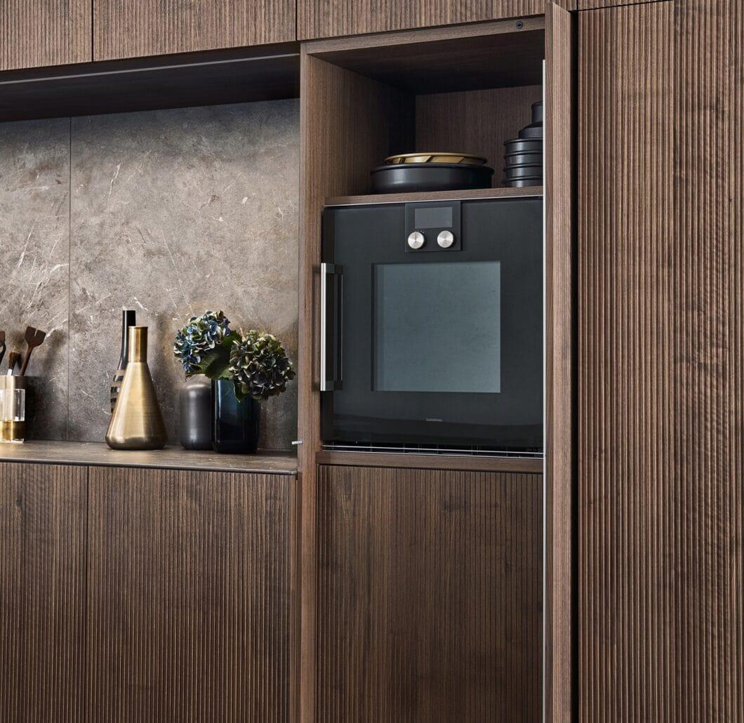 Der Einschubtürenschrank verbirgt Einbaugeräte wie Backofen oder Kühlschrank vollständig und sorgt für eine geschlossene, harmonische Optik. (Foto: LEICHT)