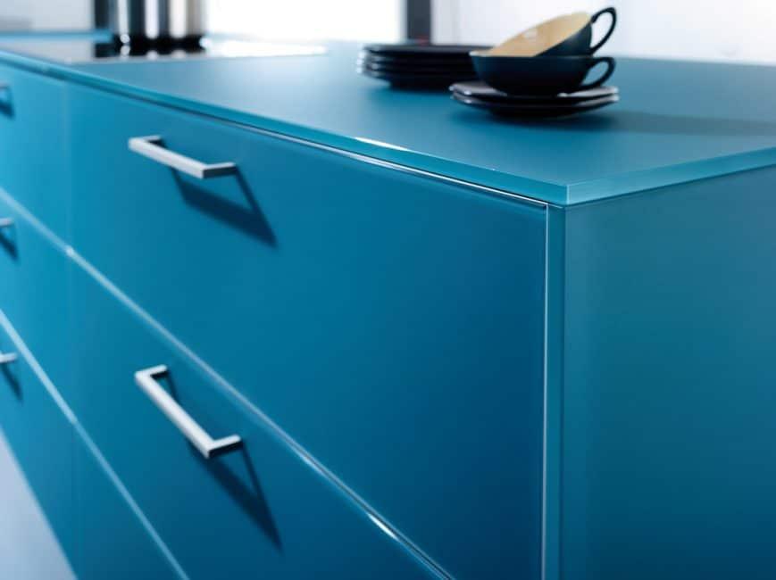 Die Retro-Designfarbe Petrol kommt bei der Largo-FG-Reihe bei Küchenfronten und Arbeitsplatte gleichermaßen zur Geltung. Die Glas-Keramik-Konstruktion in matt beruhigt den aufwändigen Farbton, dazu kombiniert der Hersteller Oberschränke in lichtem Grau und Lack. Küche: Leicht