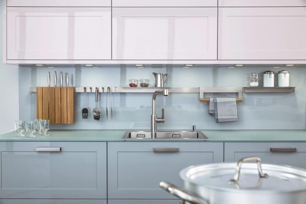 Die Carré-2-FG von Leicht spielt mit Material und Farbe: Klassische, hochglänzend lackierte Rahmenfronten weisen ein arktisches Weiß bei den Hochschränken und ein helles Blaugrau im Unterschrankbereich auf. Die Arbeitsfläche besteht aus mattem, gehärteten Glas. Küche: Leicht