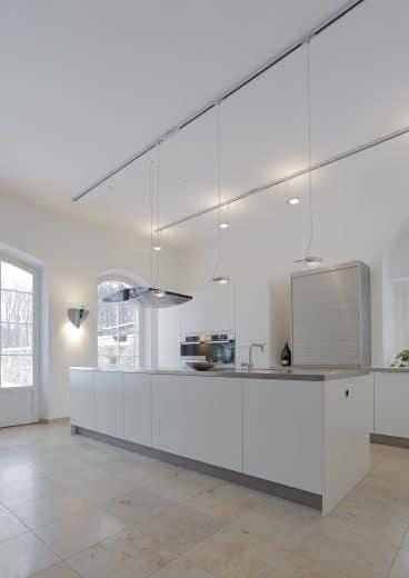 Eine puristische weiße Küche von eggersmann passt sich den lichtdurchfluteten Räumlichkeiten an und wirkt doch sehr elegant in den alten Räumlichkeiten der Orangerie. (Foto: Bodo Mertoglu)