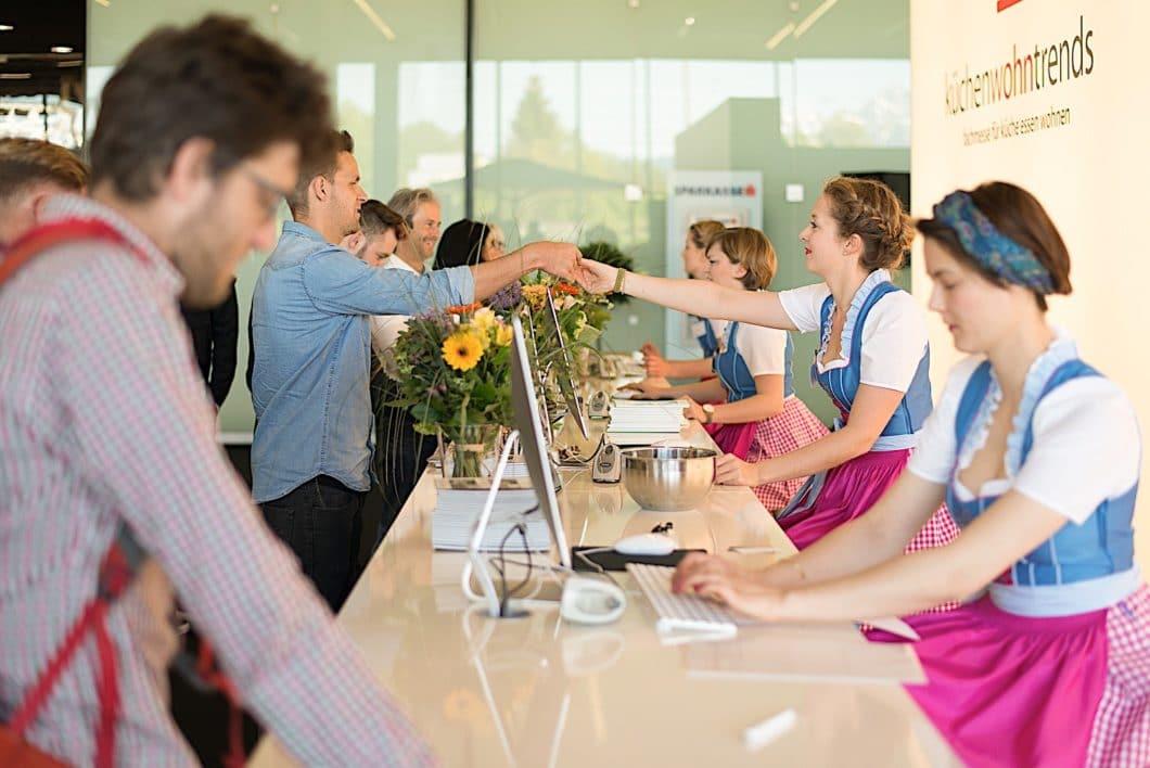 Mitarbeiterinnen begrüßen Fachbesucher auf der küchenwohntrends in Salzburg zünftig im Dirndl. Auch sonst die Fachmesse sehr entspannt. (Foto: trendfairs GmbH)