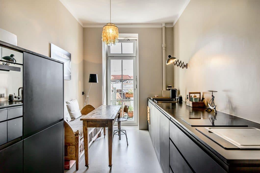 Im ebenfalls schwarz geölten Einbauschrank wurden Kühlschrank und Backofen untergebracht. Gemeinsam mit dem rustikalen Holztisch und entsprechender Beleuchtung ergibt sich ein modernes, industrielles Wohnflair. (Foto: Ludwig 6)