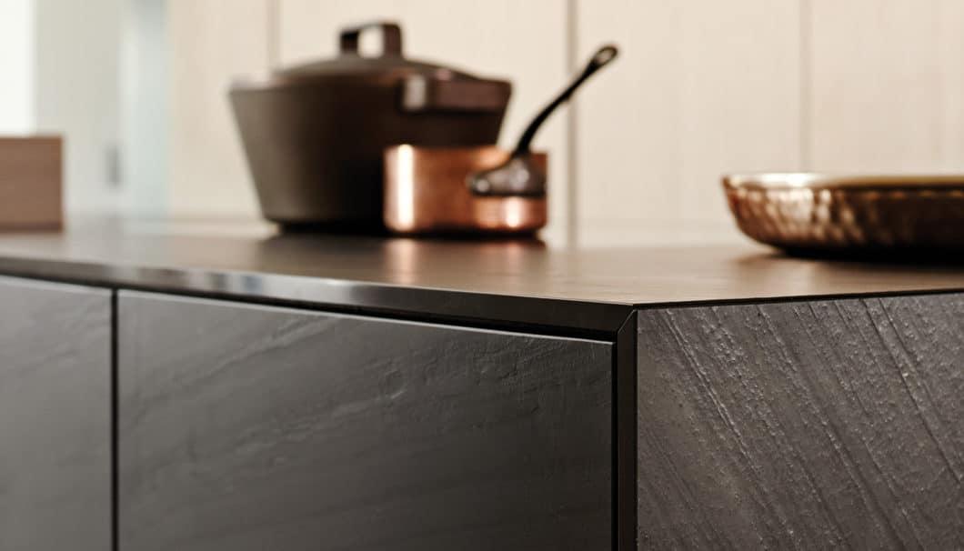 Schwarzer Phyllit mit einer angenehmen Haptik bildet die puristische Kücheninsel, in die Kochfeld und Spüle eingelassen sind. (Foto: eggersmann)