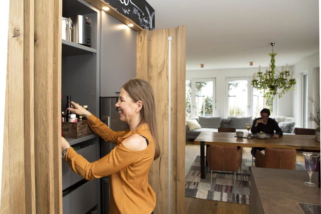 Nach außen hin puristisch gestaltet, verbirgt sich hinter der charakteristischen Altholzwand viel Stauraum für Einbaugeräte und Küchenutensilien. (Foto: küchenART München)