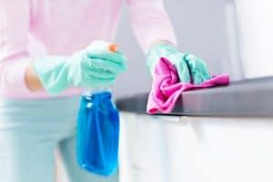 (Bild: piksel) - Frau reinigt Küchenfront und Arbeitsplatte