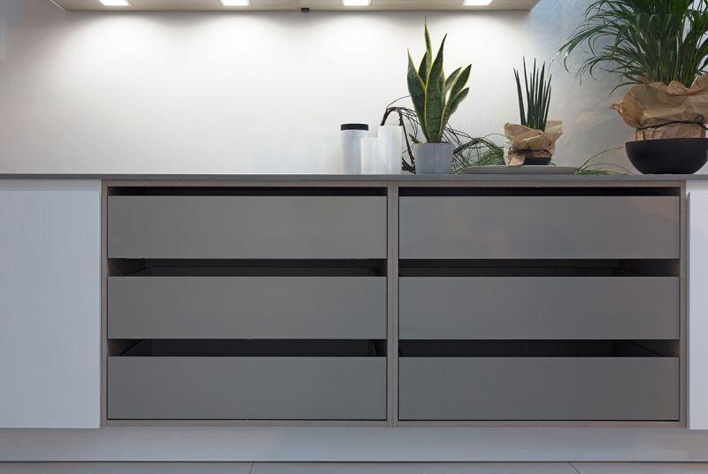 Eine Abwechslung in den kühlen, weißen Küchenraum bringt dieser Schrank ohne Fronten in einem weichen Tessilo-Grau, der schnellen Zugriff auf die Küchenutensilien ermöglicht. (Foto: Rotpunkt)