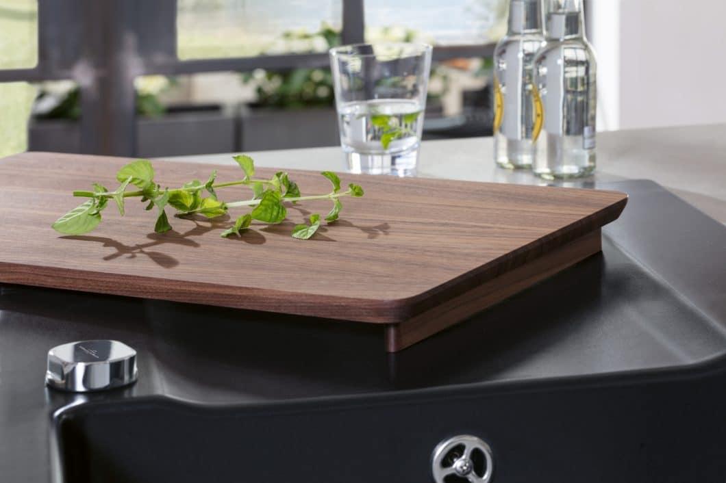 Die minimalistische Küchenspüle aus TitanCeram kann durch passgenaues Zubehör - wie dieses Schneidbrett aus Nussbaum - in ihrer Funktionalität erweitert werden. (Foto: Villeroy & Boch)