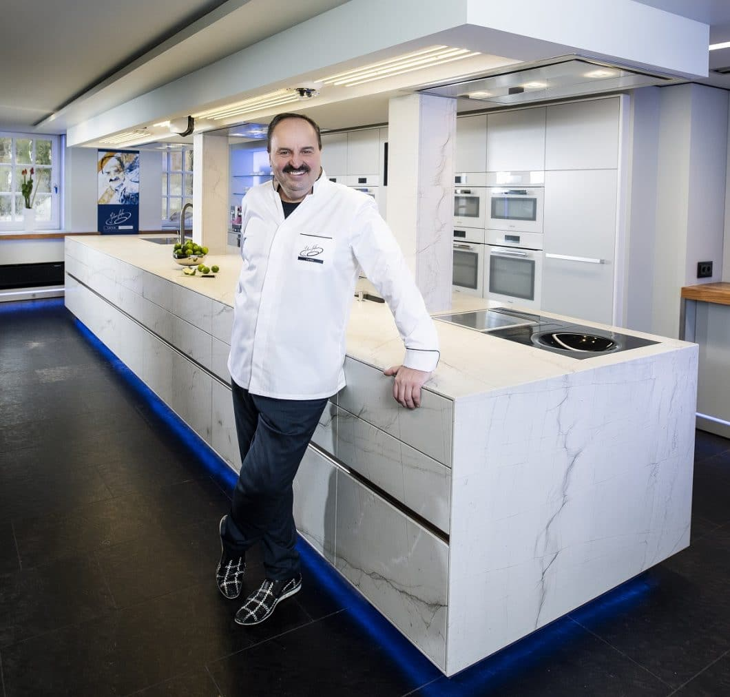 Hat gut zu lachen: auf dieser beeindruckend langen Kücheninsel von ST-ONE kann TV-Starkoch Johann Lafer künftig viele Kochschüler zum Anpacken animieren. (Foto: STRASSER Steine)