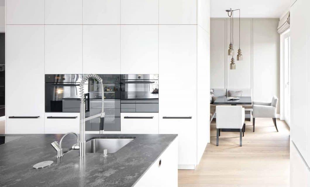 Auch die Küchenwand selbst kann als Zonierung genutzt werden: Dank geschickter Planung steht diese Wand in der Mitte des Raumes. Sowohl Küchen- als auch Wohnzone richten sich zum Fenster hin aus. (Foto: Dross & Schaffer Ludwig 6)