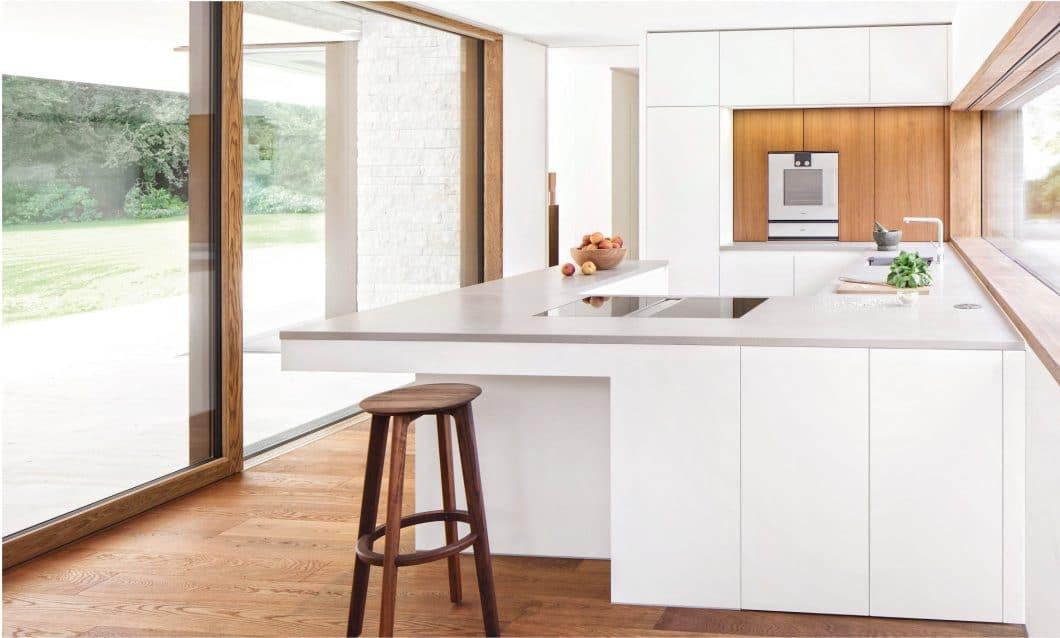 """Das Modell """"Küche voller Licht"""" spricht für sich selbst: Mit sanften Mattlack-Fronten wird hier das Tageslicht reflektiert und flutet den Raum mit Helligkeit. Als sanfte Abgrenzung dienen eine Arbeitsplatte aus QuarzComposit BetonArt und eine holzverkleidete Rückwand. (Foto: selektionD)"""